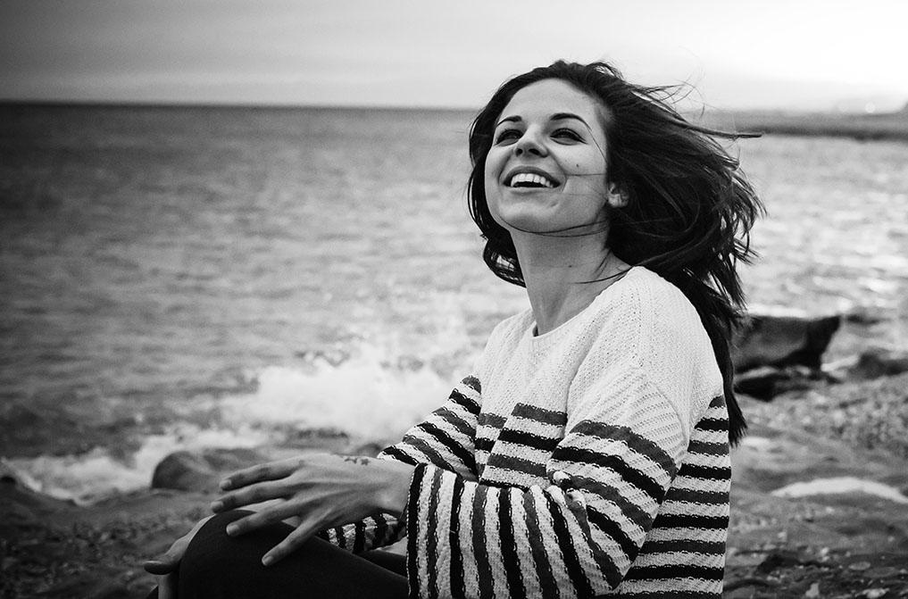 Reportaje moda, muchacha en El Toyo, Retamar. Riendo en la playa