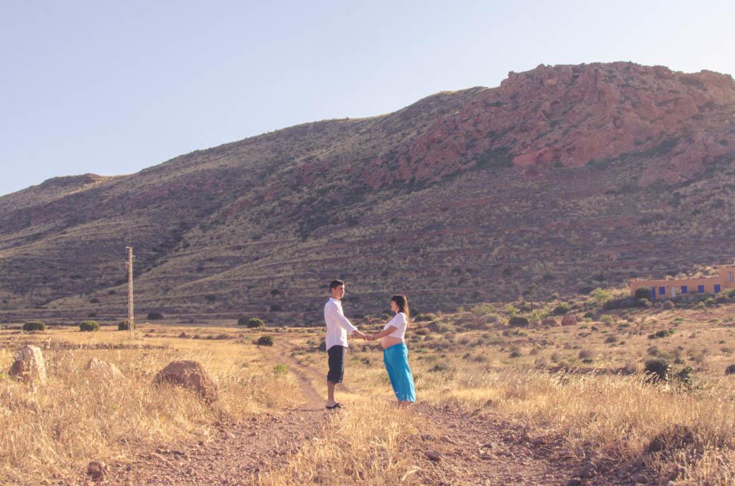 pareja embarazada dandose las manos en paisaje veraniego-fotógrafos de bodas almería -blow up photo